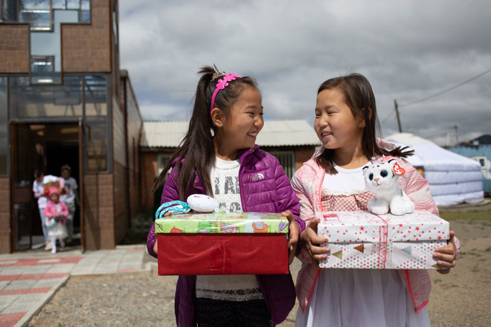 Friends share a smile over shoebox gifts