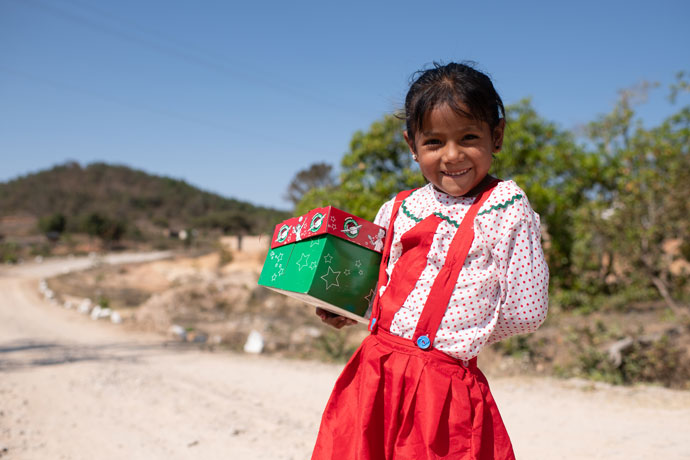 Little girl in red dress with shoebox gift
