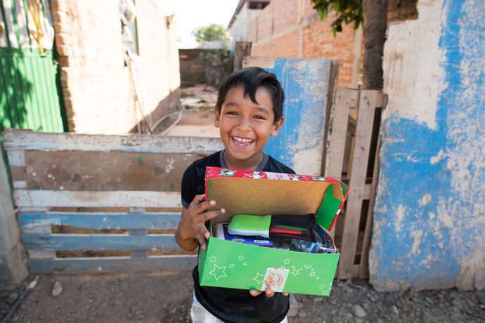 Little boy smiles with open shoebox