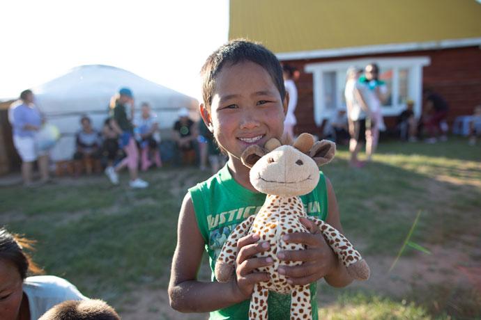 Boy holding cuddly toy giraffe