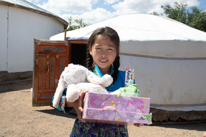 Little girl smiles with a shoebox gift and cuddly toy
